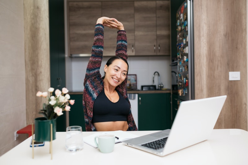 A person stretches her arms over her head while looking at her laptop at home. Stretching can help improve your mental health.