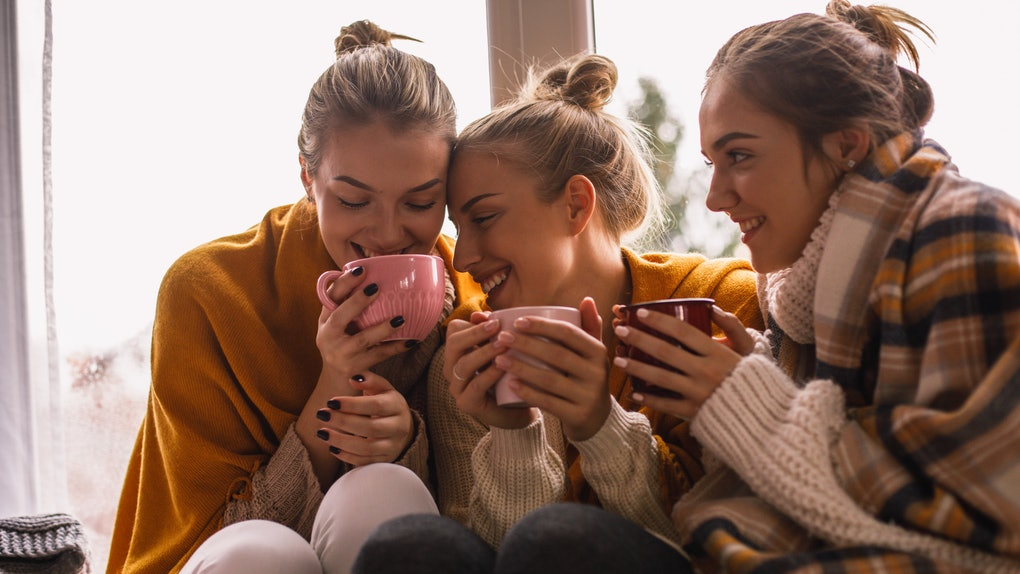 Three girls bundled up for fall hold mugs while sitting in front of a bright window.
