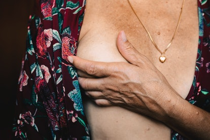 A person conducts a breast self-exam wearing a floral dressing gown.