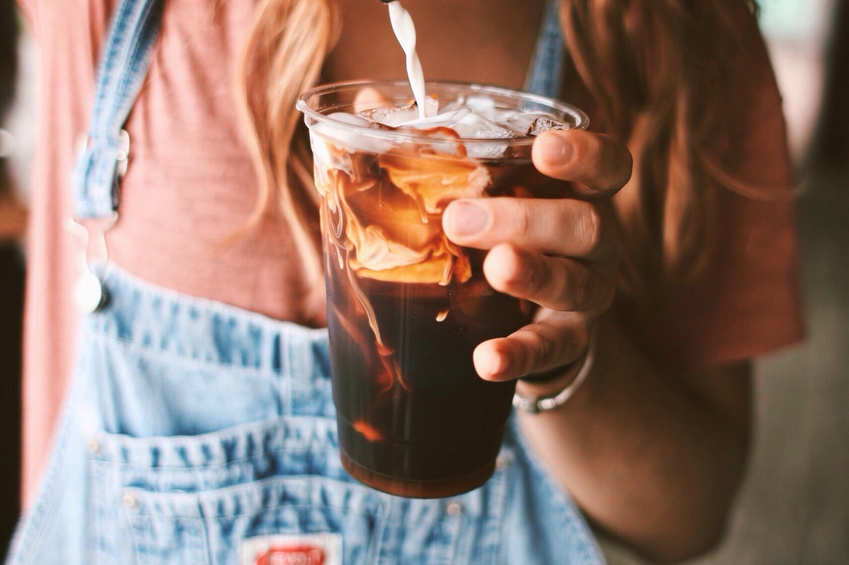 A woman wearing overalls, pours some milk into her cold brew drink.