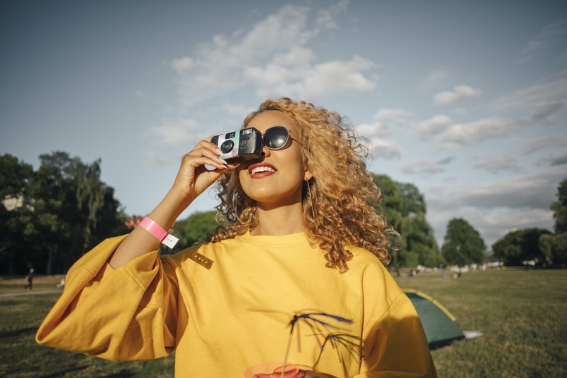 A woman with blonde natural hair takes a photo with a disposable camera. A human memory researcher explains what causes deja vu in your brain.
