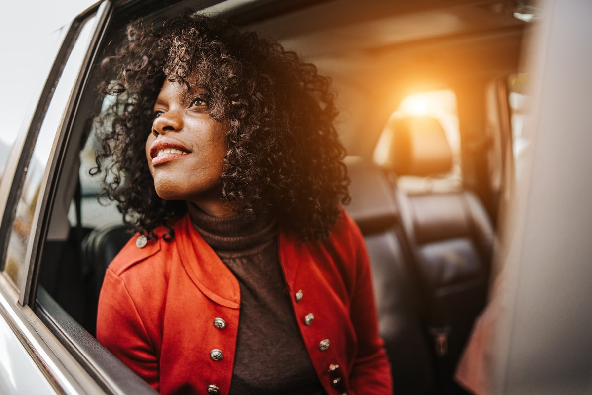 A young Black woman looks out her car window while going through a drive-thru fall experience.