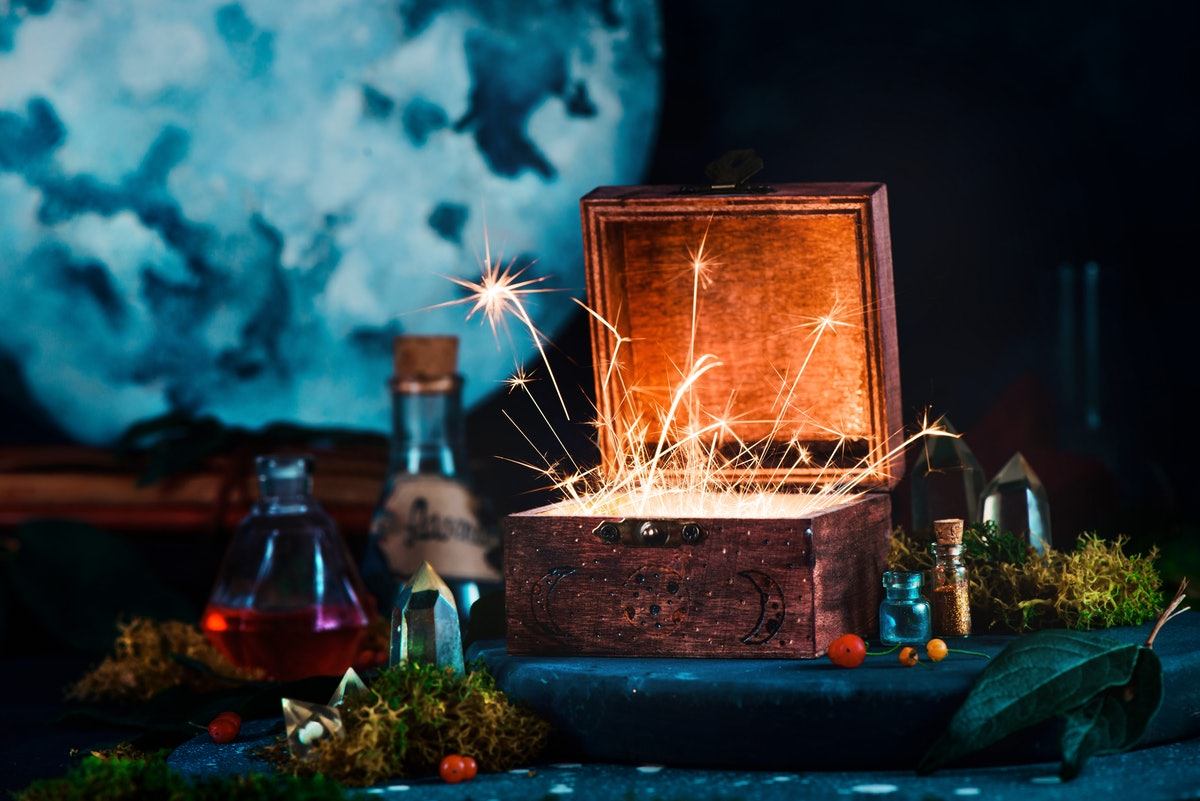 A box with sparks coming out of it is surrounded by spooky potions and crystals.