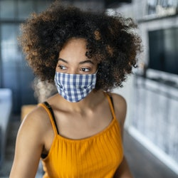 A woman with natural hair wears a blue gingham mask. Doctors debunk 8 myths about wearing face masks.
