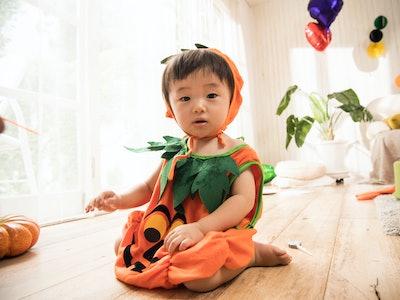 baby in pumpkin costume inside halloween