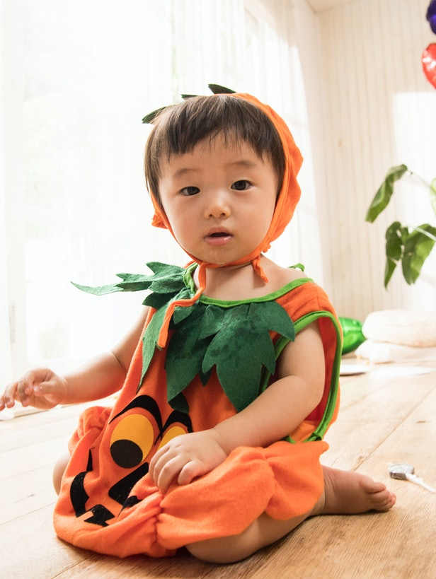 baby in pumpkin costume inside halloween