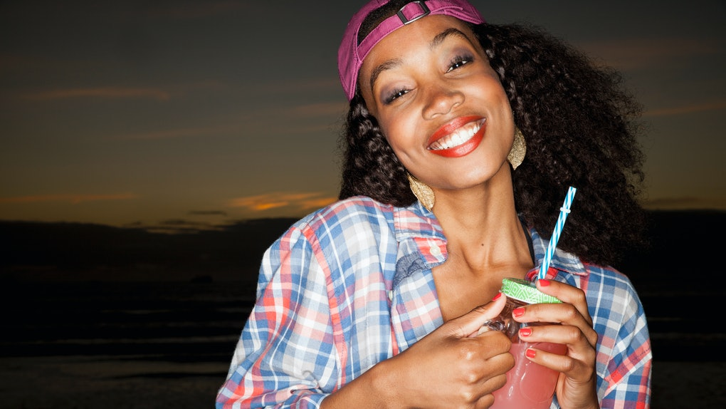A happy woman wearing a backwards baseball cap and flannel shirt holds a mason jar with a wine slushie in it.