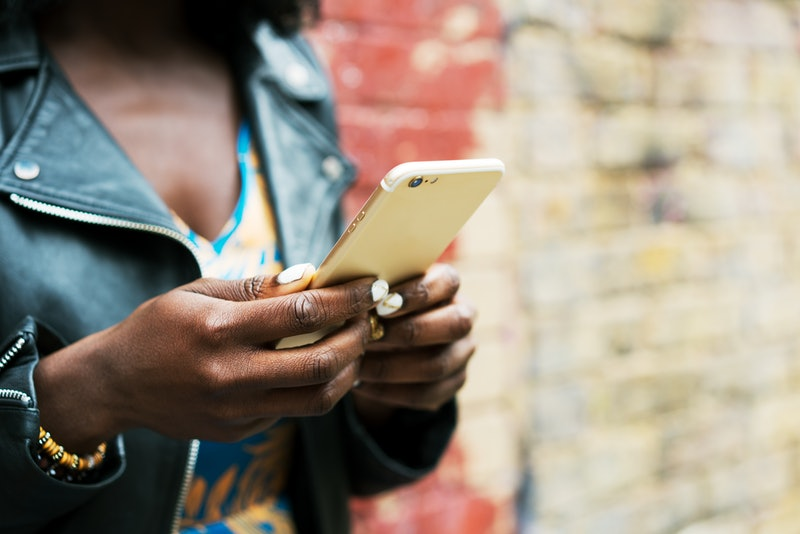 A woman in a leather jacket looks at instagram on her phone. Experts explain that instagram does have positive impacts on mental health