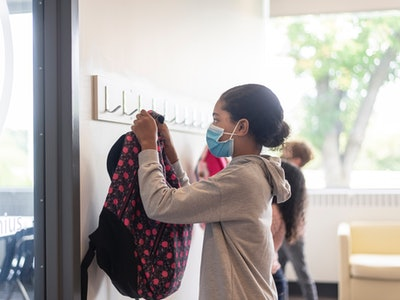 girl hanging up backpack wearing face mask