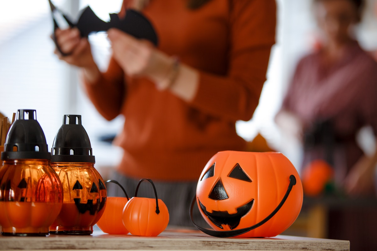 A pumpkin bucket sits on the table, as a woman cuts a bat decoration in the kitchen.