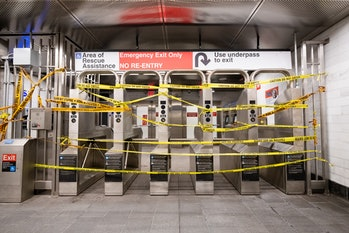 The entrance to the NYC subway system covered in caution tape.