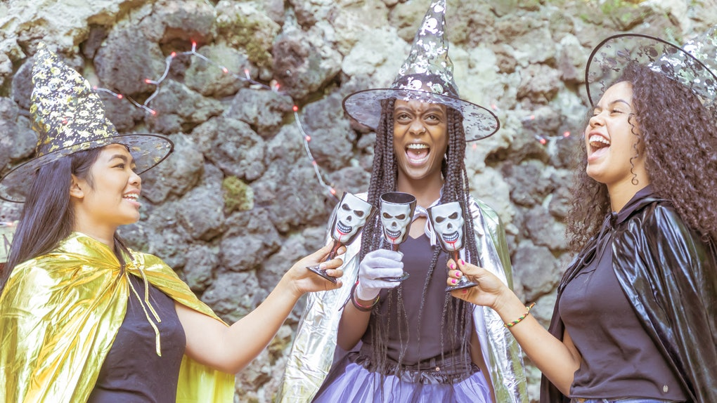 Three women dressed as witches laugh while they clink their skeleton glasses.
