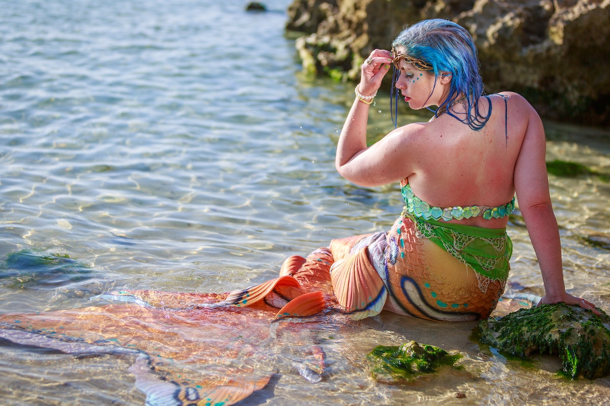 A woman with blue hair and a mermaid tail on poses in the water.