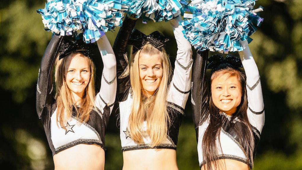 Three cheerleaders raise their pom poms over their heads.