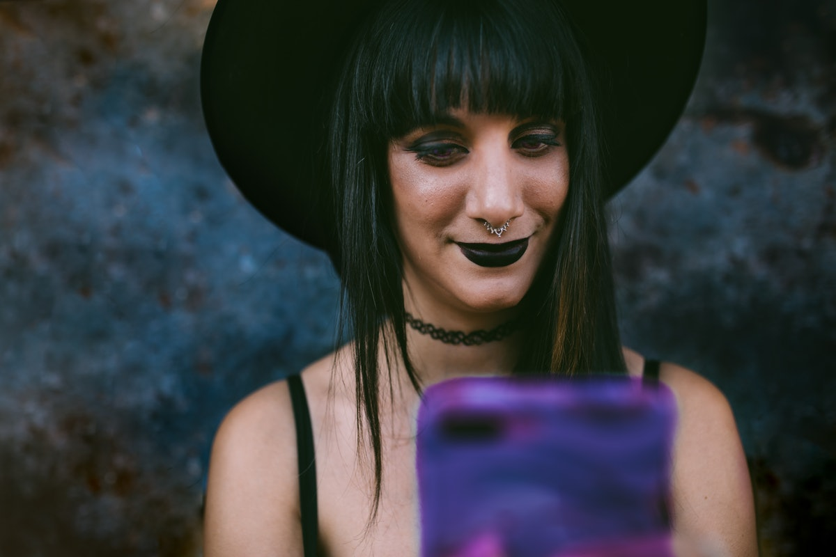 A woman with black lipstick, a black tank top, and a black witch's hat smiles and takes a selfie on Halloween.