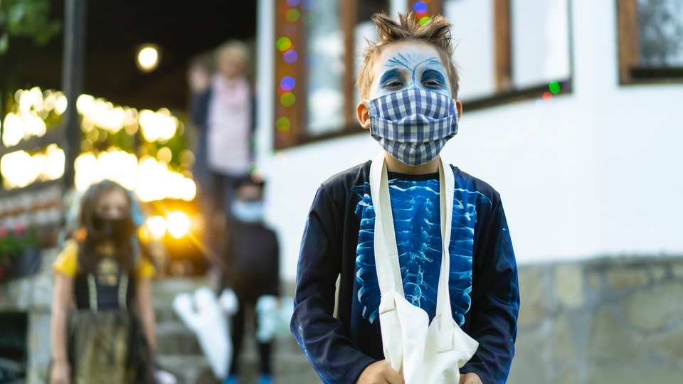 kid with face mask on halloween