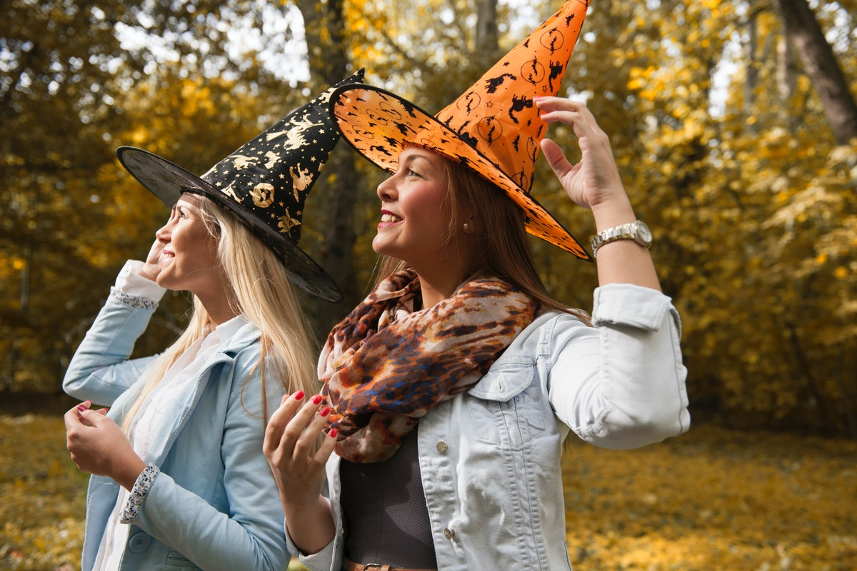 Two women wearing witch hats smile and look at the sky.
