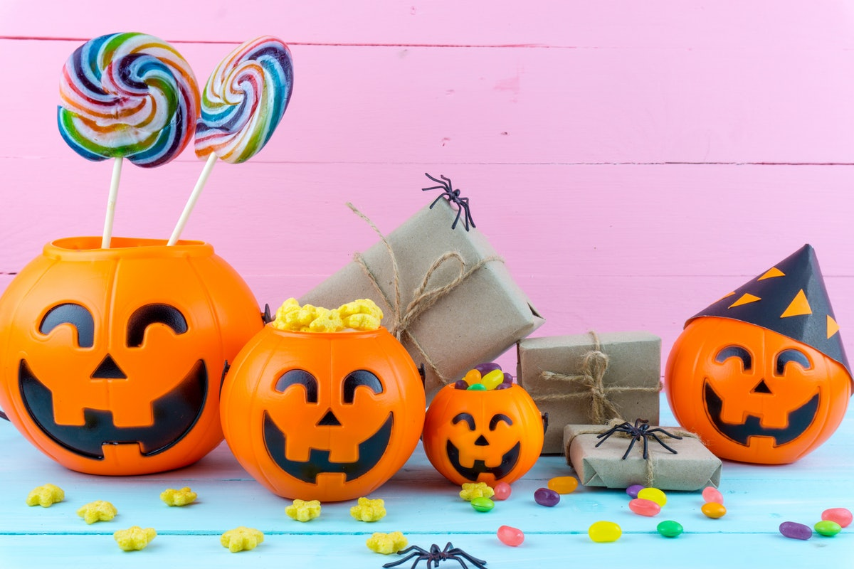An assortment of plastic jack-o-lanterns, filled with candy, sits on a table next to a pink wall.
