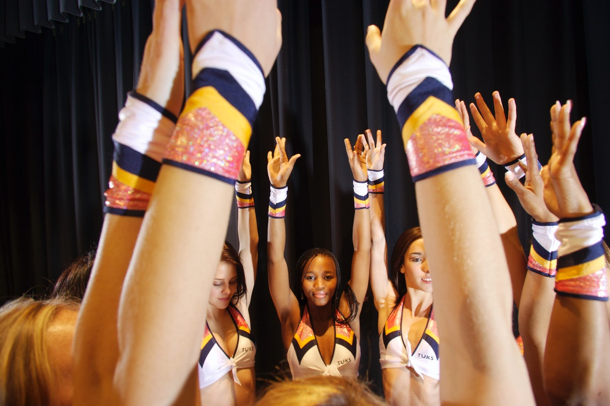 A group of cheerleaders huddle up in a circle with their arms in the air.