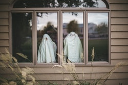kids dressed up like ghosts in window of haunted house