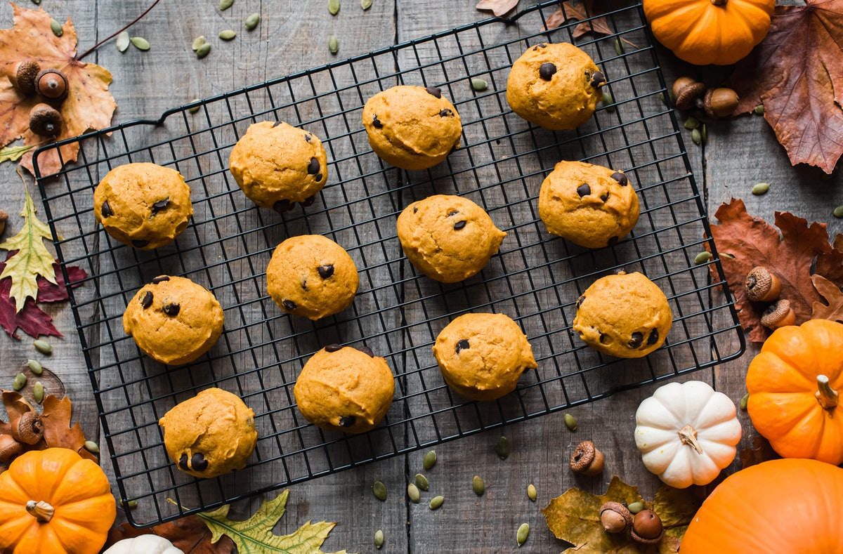 Pumpkin spice cookies with chocolate chips sit on a rack with pumpkins and fall leaves surrounding i...