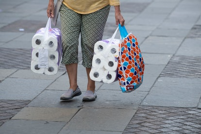 woman carrying two large packs of loo roll