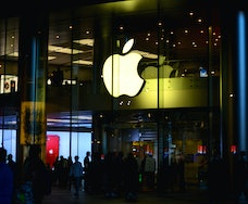 The Apple logo appears inside a retail store.