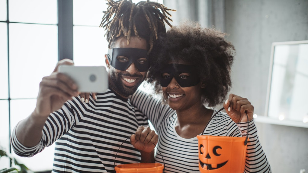 A young Black couple holds up pumpkin baskets while taking a selfie on Halloween.