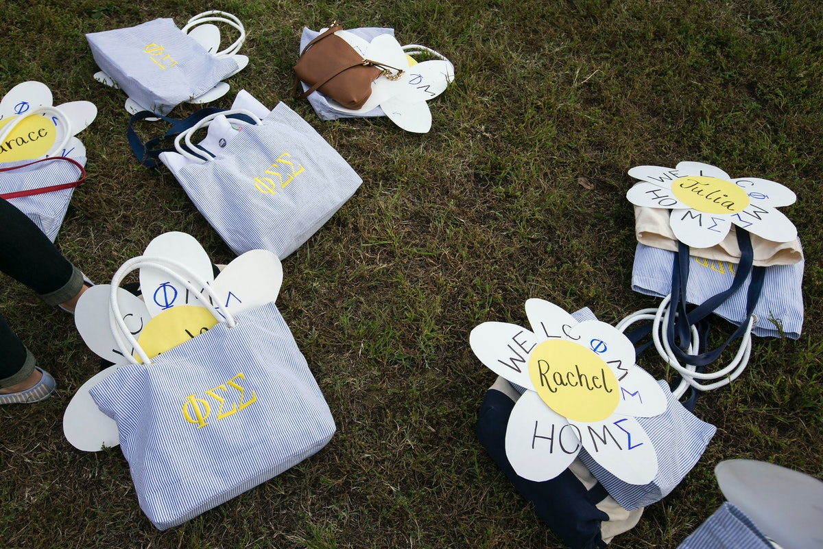 Striped totes filled with crafts and goodies for new sorority members lay on the grass.