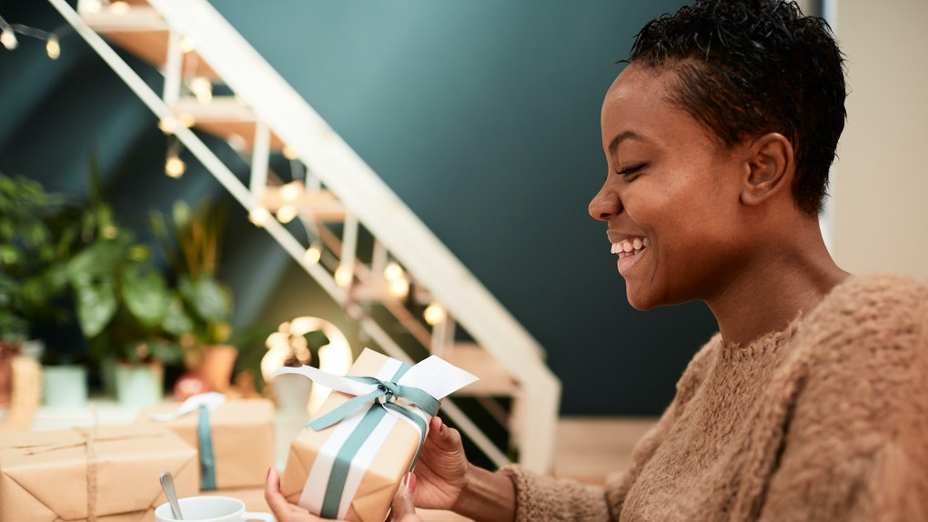 A happy woman wraps a Christmas gift with a bow.