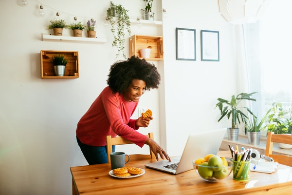A young Black woman video chats with her friends while eating a dessert in her kitchen.