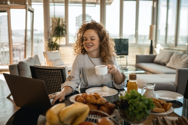 A young woman with curly red hair sits at a table with her laptop and video chats with friends while eating breakfast food.