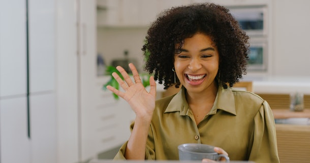A young Black woman waves at her laptop while video chatting with friends and drinking coffee.