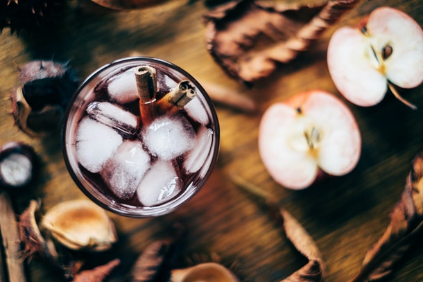 A autumn cocktail sits on a wooden table with sliced apples.
