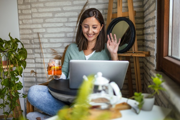 A young woman waves to friends she's video chatting with while drinking tea and sitting near plants.