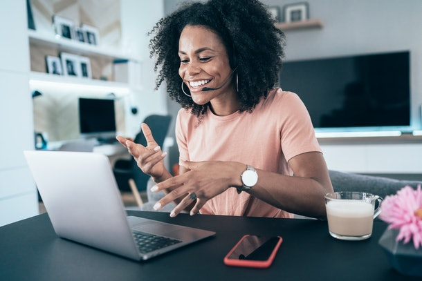 A happy woman laughs while talking to someone on her laptop via video chat in her apartmenr.