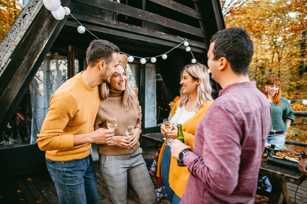 Two trendy couples smile and enjoy drinks on the deck of a cabin for a Friendsgiving gathering.