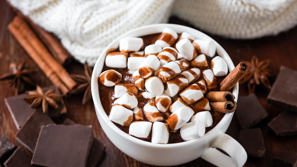 A cup of hot chocolate with marshmallows sits on a wooden table with chunks of chocolate, cinnamon sticks, and a white blanket.