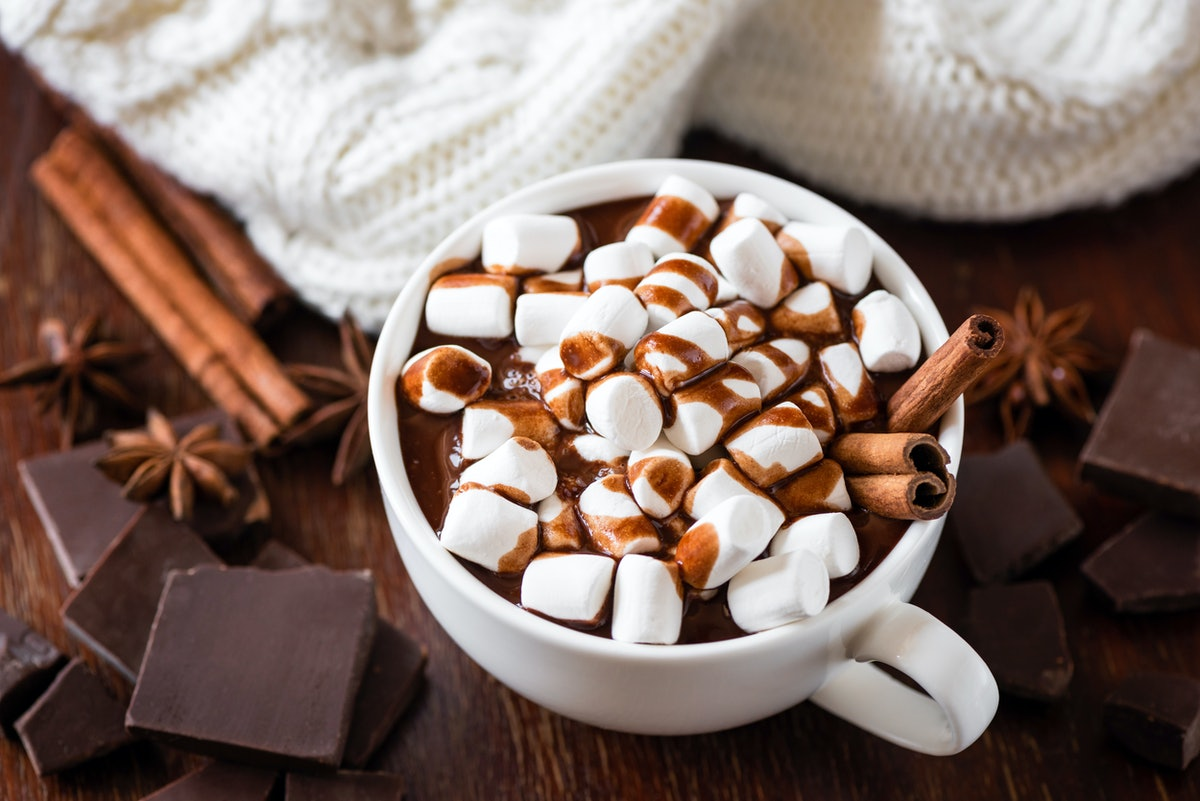 A cup of hot chocolate with marshmallows sits on a wooden table with chunks of chocolate, cinnamon s...