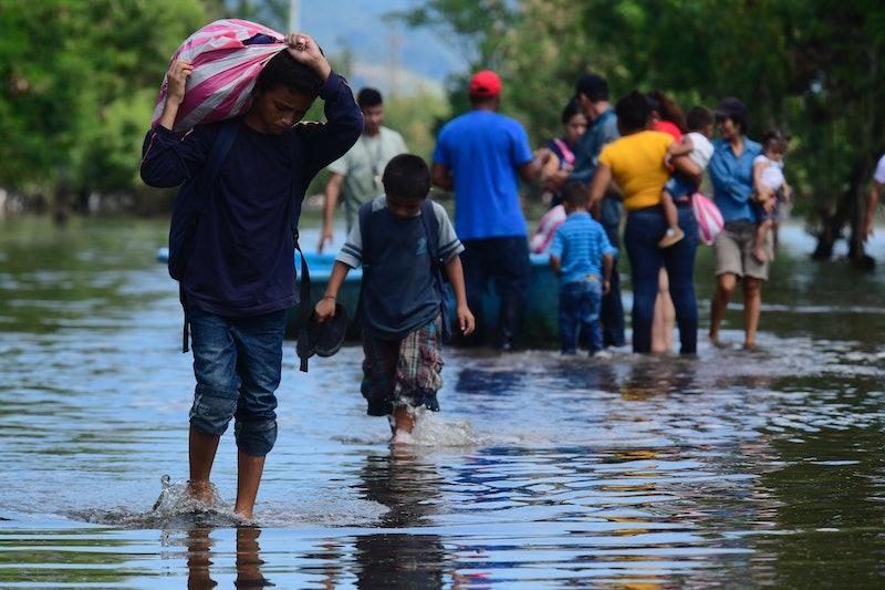 Survivors of Hurricane Eta move supplies across flooded regions.