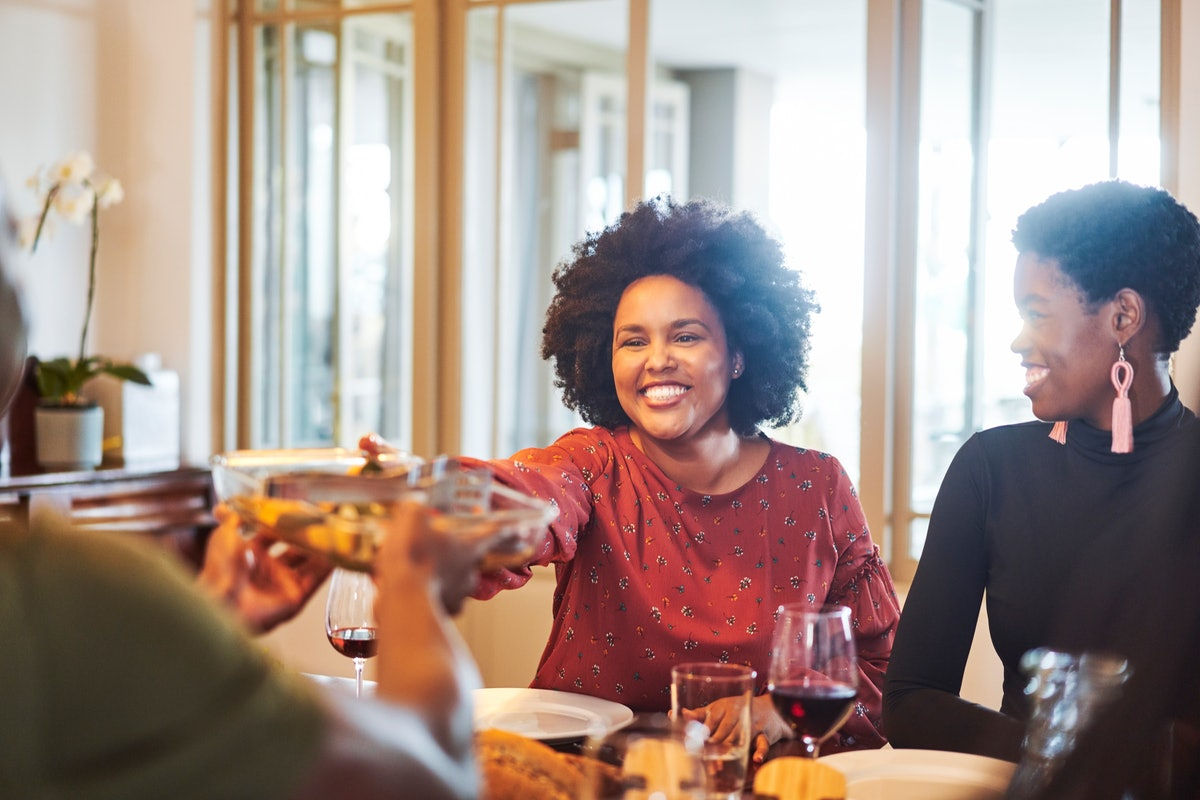 Two women laugh while enjoying a Thanksgiving dinner.