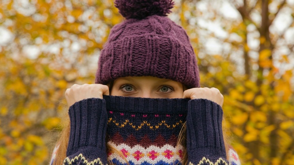A woman wearing a beanie holds up her sweater over her mouth, while standing outside in the fall.