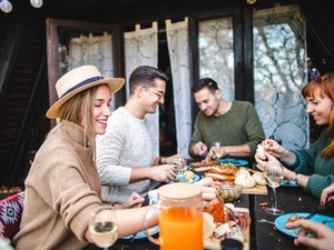A group of friends enjoys meats and cheese outside on a cabin's deck in the woods.