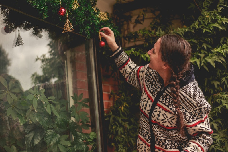 A woman in a fair isle sweater hangs up christmas ornaments. Dealing with loneliness around the holidays? Experts have tips for that.