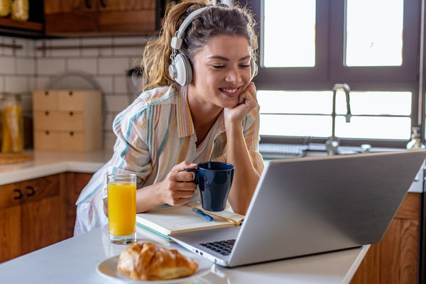 A happy woman with headphones and a striped button-down shirt on holds a coffee mug while smiling at her laptop screen.
