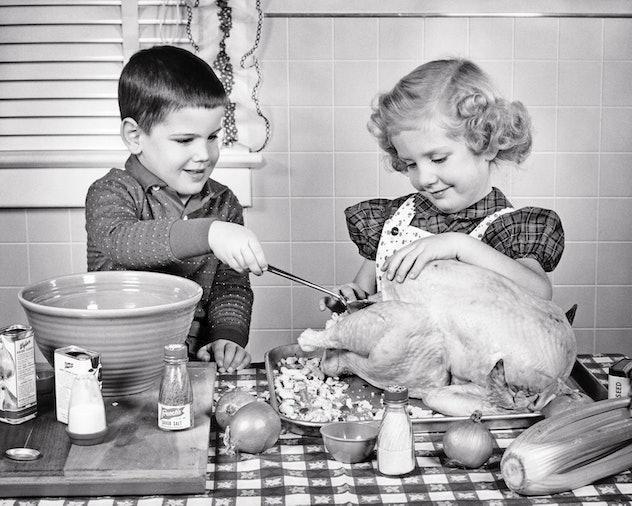 Children stuffing a Thanksgiving turkey.