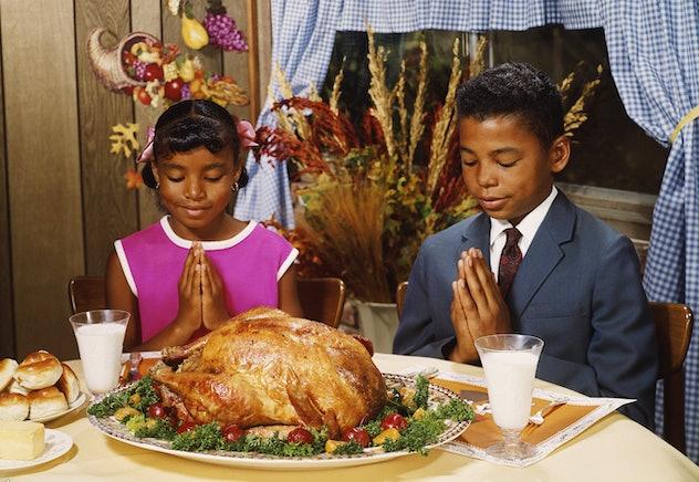 Siblings praying before Thanksgiving dinner.