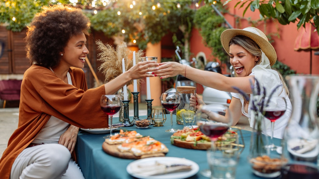 Two trendy friends laugh and toast their wine glasses while enjoying a Friendsgiving meal outside.