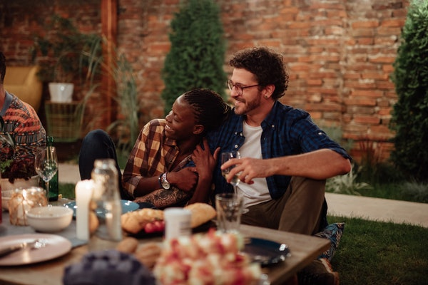 A happy couple enjoys a backyard picnic with friends for Friendsgiving.