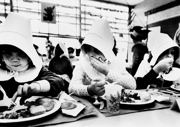 Girls dressed as pilgrims eat lunch at school.